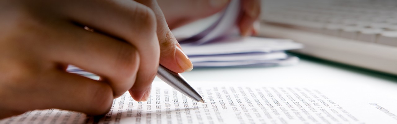 hands-holding-pen-while-reading-banner-horizontal-1440x450-image-file