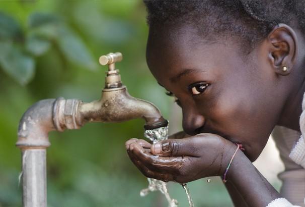 Child drinking clean water from a spiggot