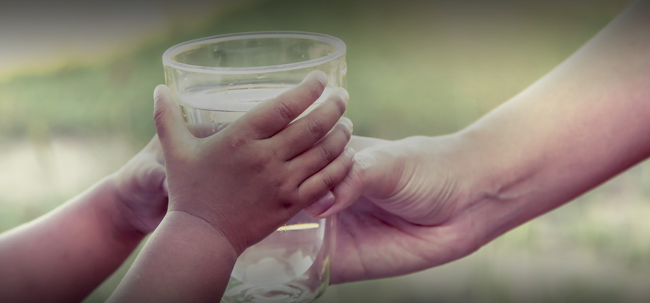 child-woman-hands-holding-water-glass-outdoor-green-grass-cropped-horizontal-1440x672-image-file