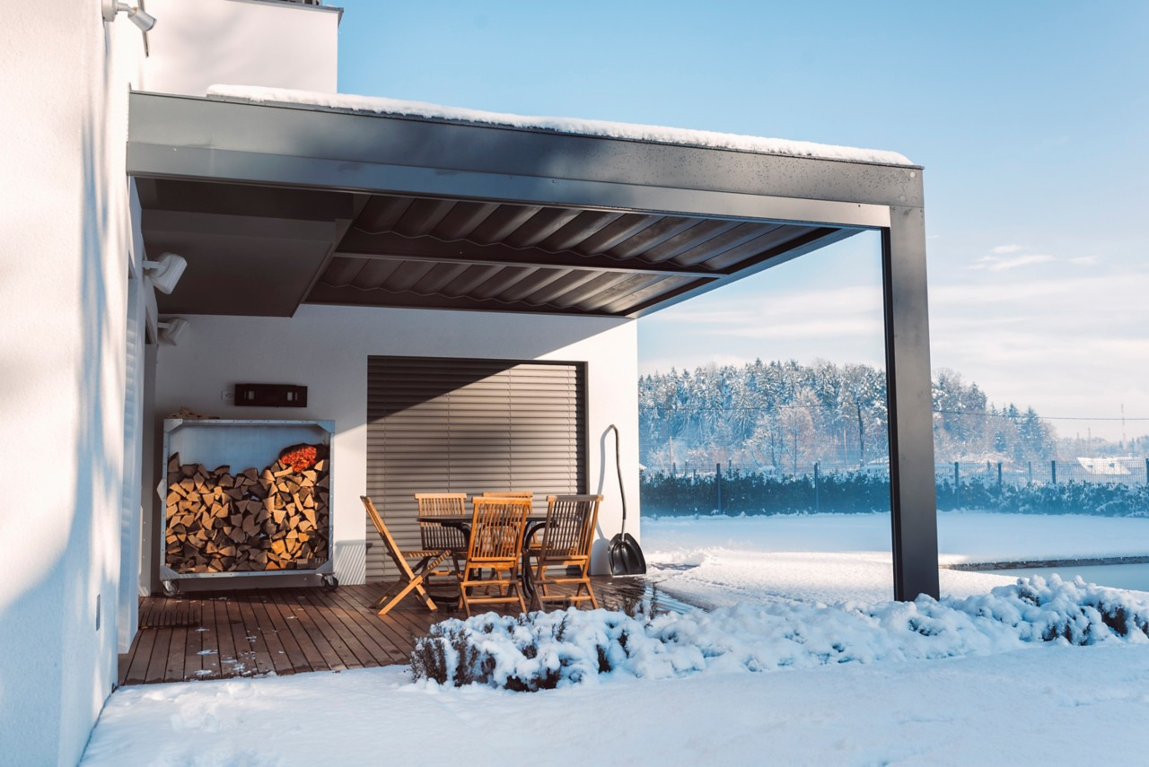 modern house in the middle of nowhere outside on deck or patio in winter with firewood and table and chairs