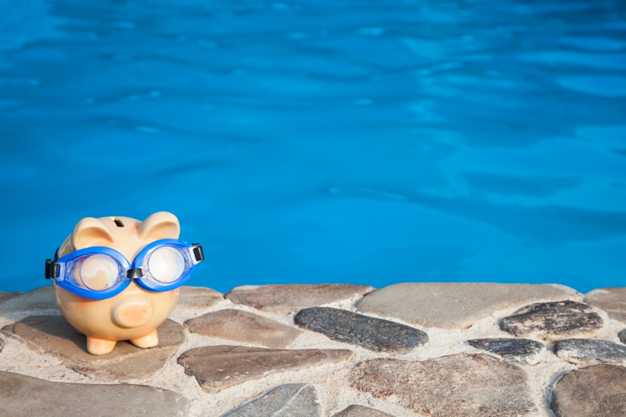 piggy bank with goggles by the pool