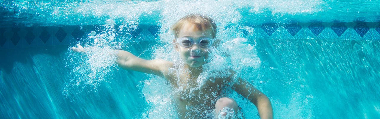 young-boy-in-pool-splash-bubbles-blue-tiles-water-1440x450-image-file