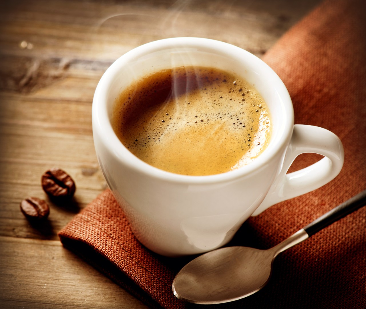 close-up-of-steaming-cup-of-coffee-in-white-mug-on-wooden-surface-with-espresso-beans-and-spoon-horizontal-7271x6136-image-file