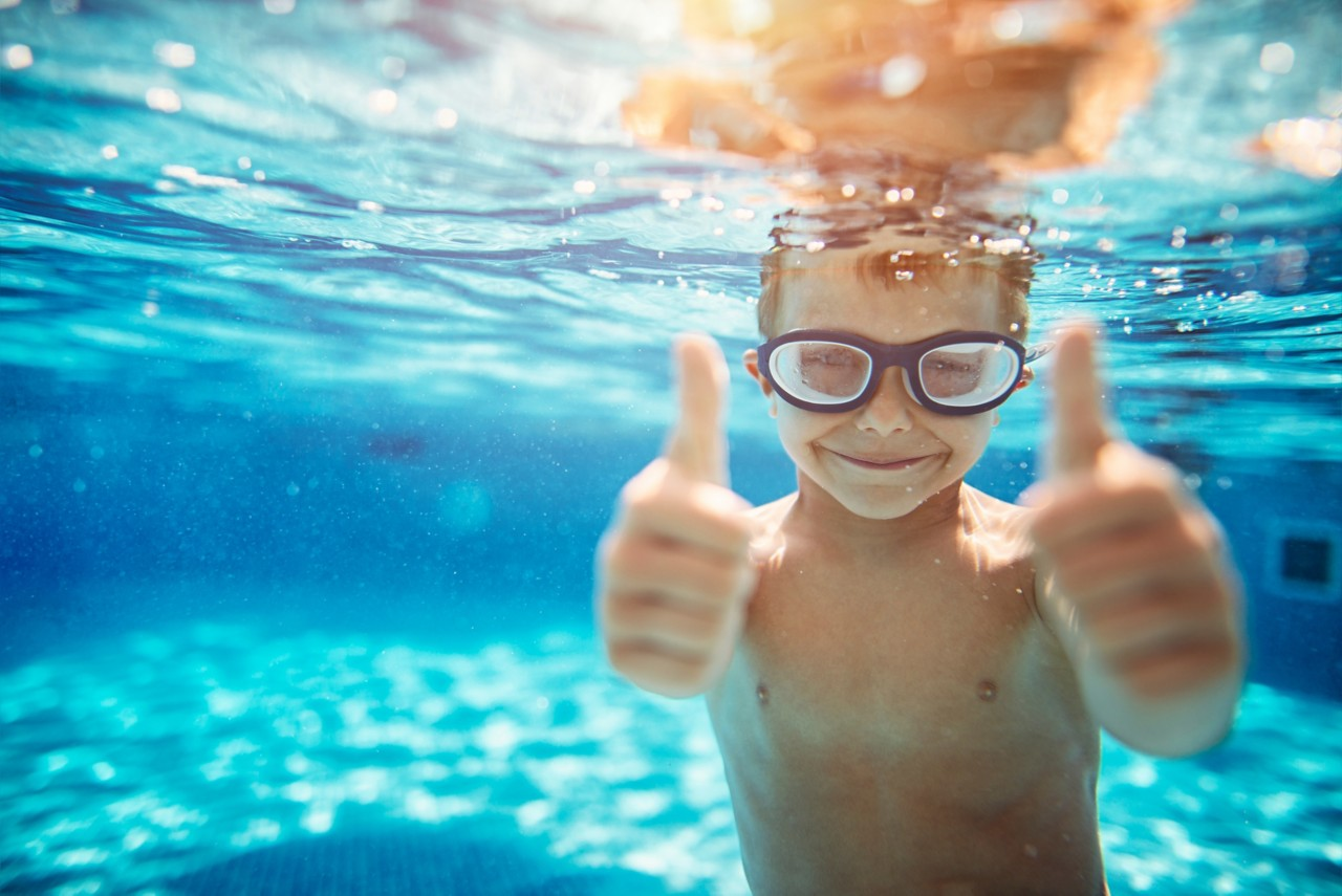 Little boy aged 6 swimming underwater. The boy is smiling at the camera showing thumbs up.