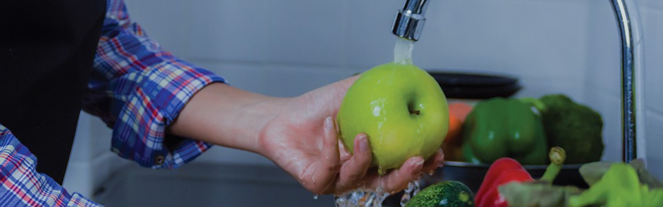Person washing apple in sink