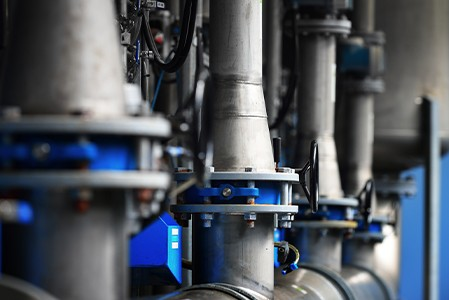 Large industrial water treatment and boiler room. Piping, flanges, and butterfly valves.