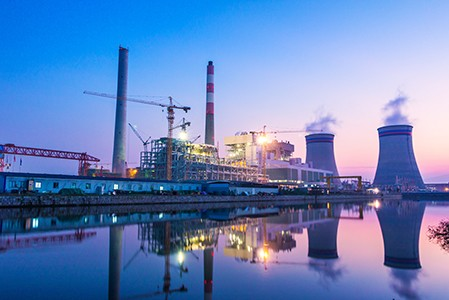A power plant with a calm body of water in front of a blue and pink sunset.
