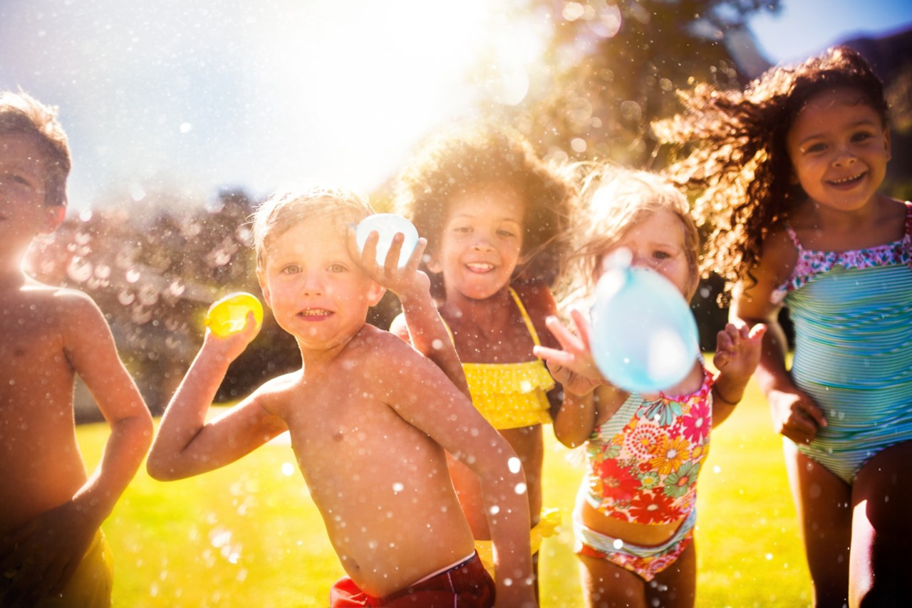 young-smiling-children-in-swimsuits-throwing-water-balloons-outdoor-on-sunny-day-horizontal-5760x3840-image-file-469932508