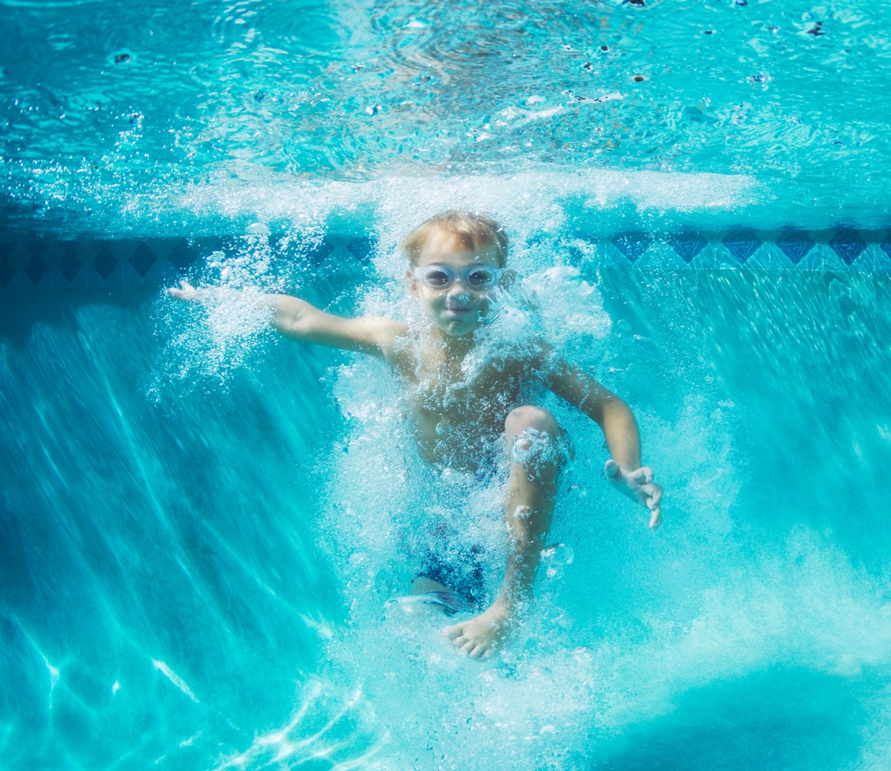 young-boy-in-goggles-jumping-into-blue-pool-underwater-with-bubbles-horizontal-3313x2867-image-file-235768561