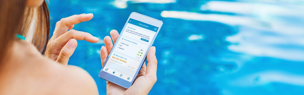 woman sitting poolside on her phone showing water chemistry on phone, pool automation