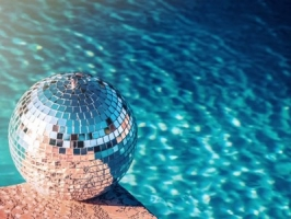 closeup of tiled pool with wooden deck and lounge chairs and pool ladder