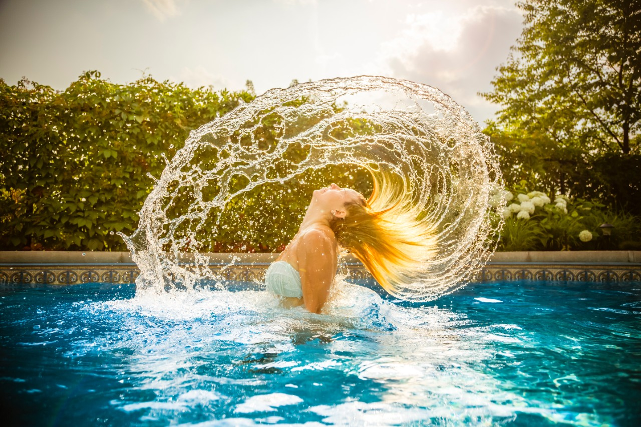Woman throwing hair back in pool