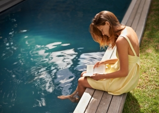 young-woman-in-yellow-dress-reading-book-by-blue-pool-outdoor-by-green-grass-on-sunny-day-horizontal-7360x5200-image-file-514613835