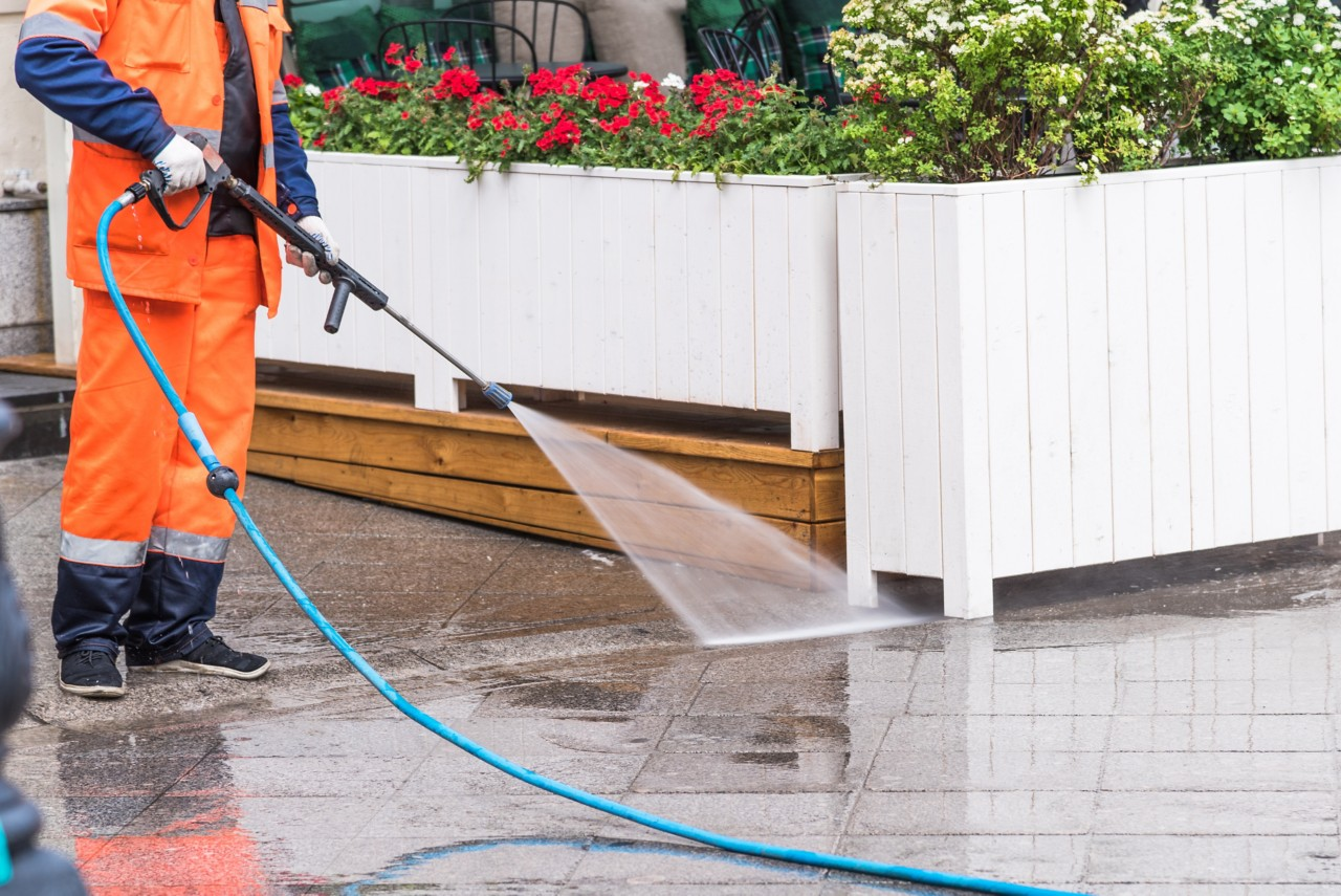 Worker washes the sidewalk in front of a street cafe - surface sanitation